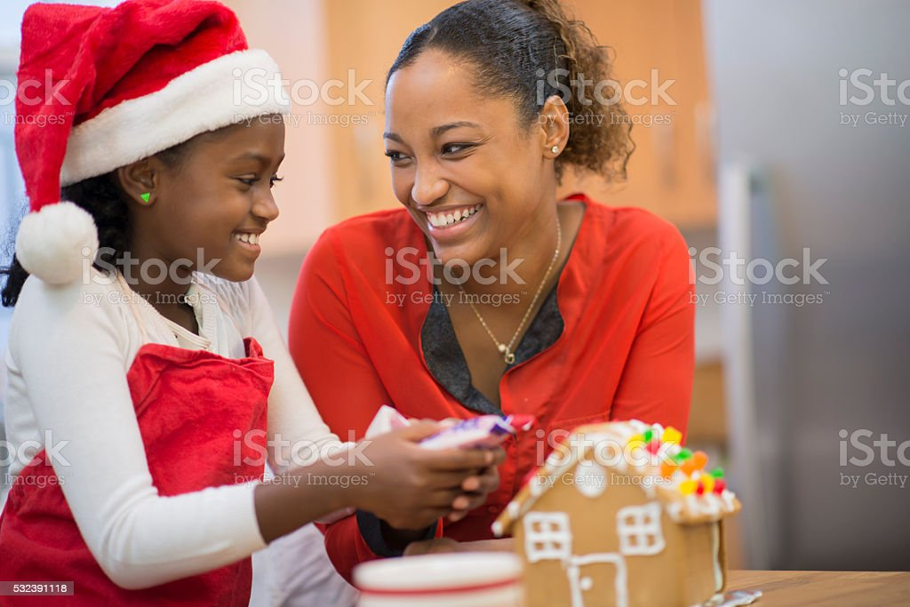 Mother and Daughter Making a Gingerbread House stock photo