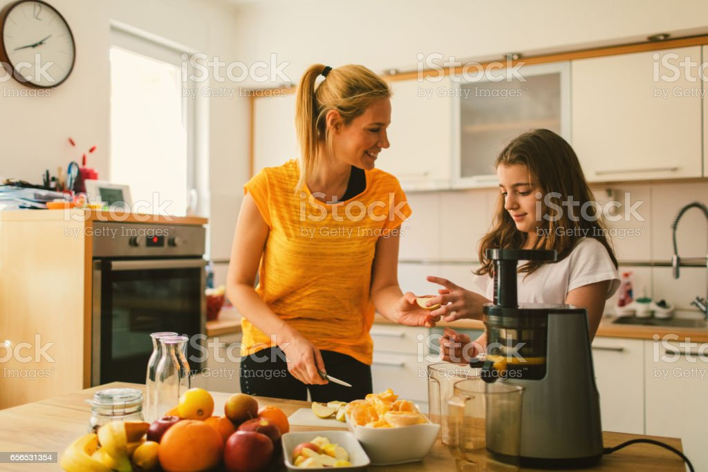 Mother and daughter making cold-pressed juice stock photo