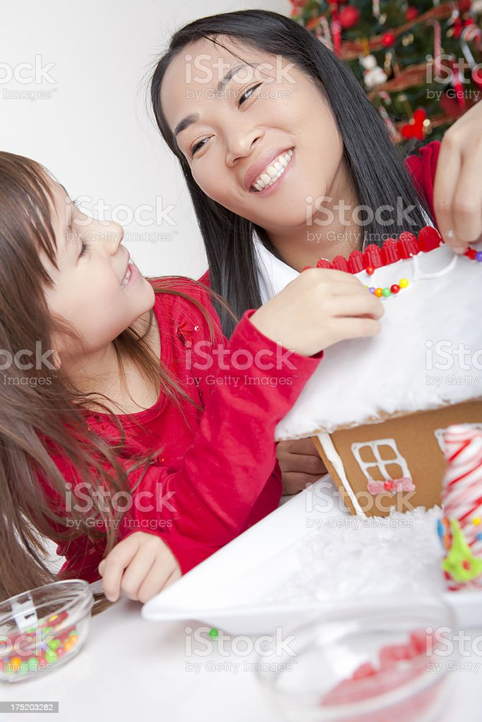 Mother and daughter making gingerbread house royalty-free stock photo