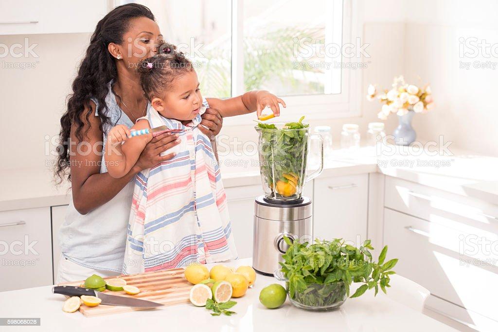Mother and daughter making lemonade. stock photo