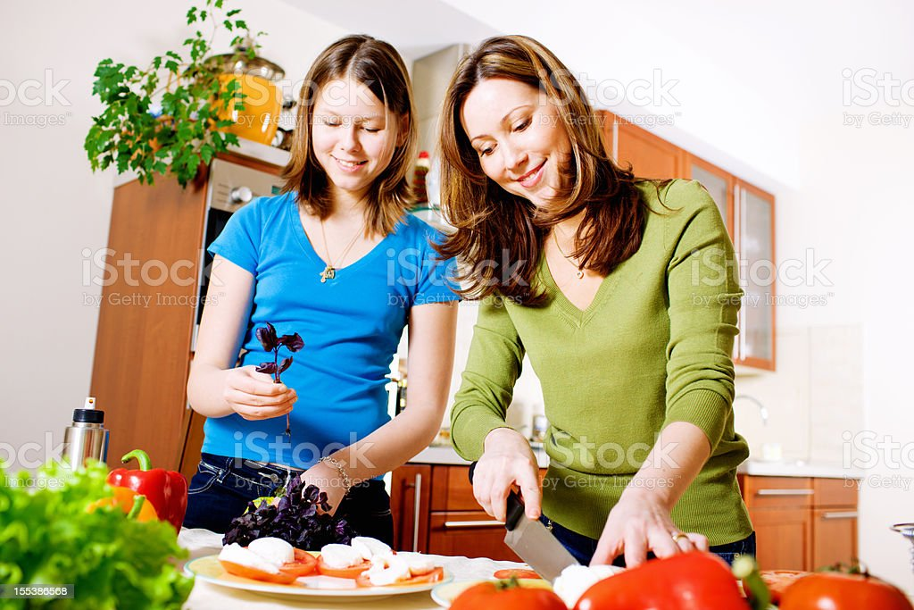 Mother and Daughter making Mozarella Salad in kitchen royalty-free stock photo