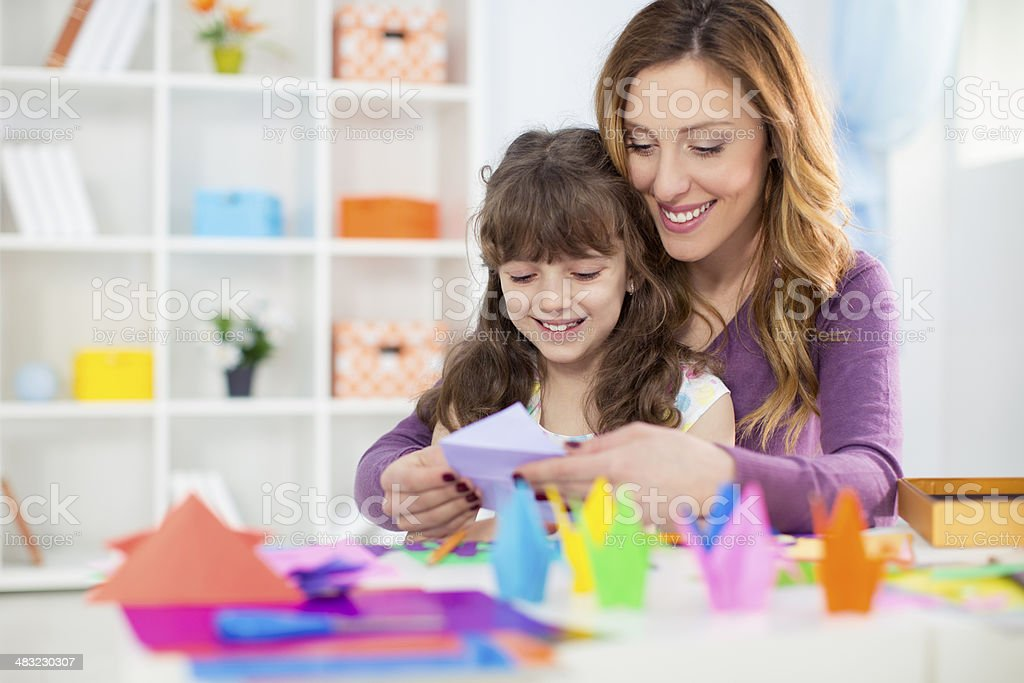 Mother and daughter making origami. stock photo