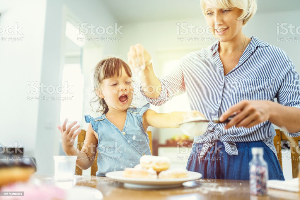 Mother and daughter making sweet donuts in the kitchen stock photo