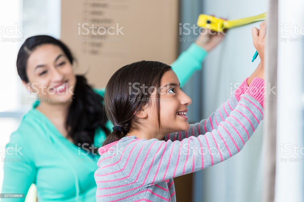 Mother and daughter measure wall in new home stock photo