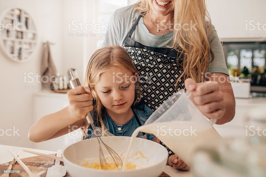 Mother and daughter mixing batter in bowl stock photo