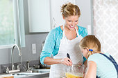 Mother and daughter mixing ingredients to bake a cake