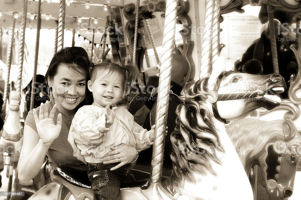 Mother and Daughter on Carousel (Sepia) stock photo