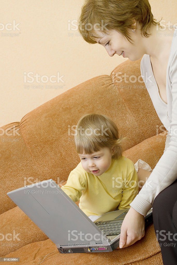 Mother and daughter on sofa with laptop royalty-free stock photo