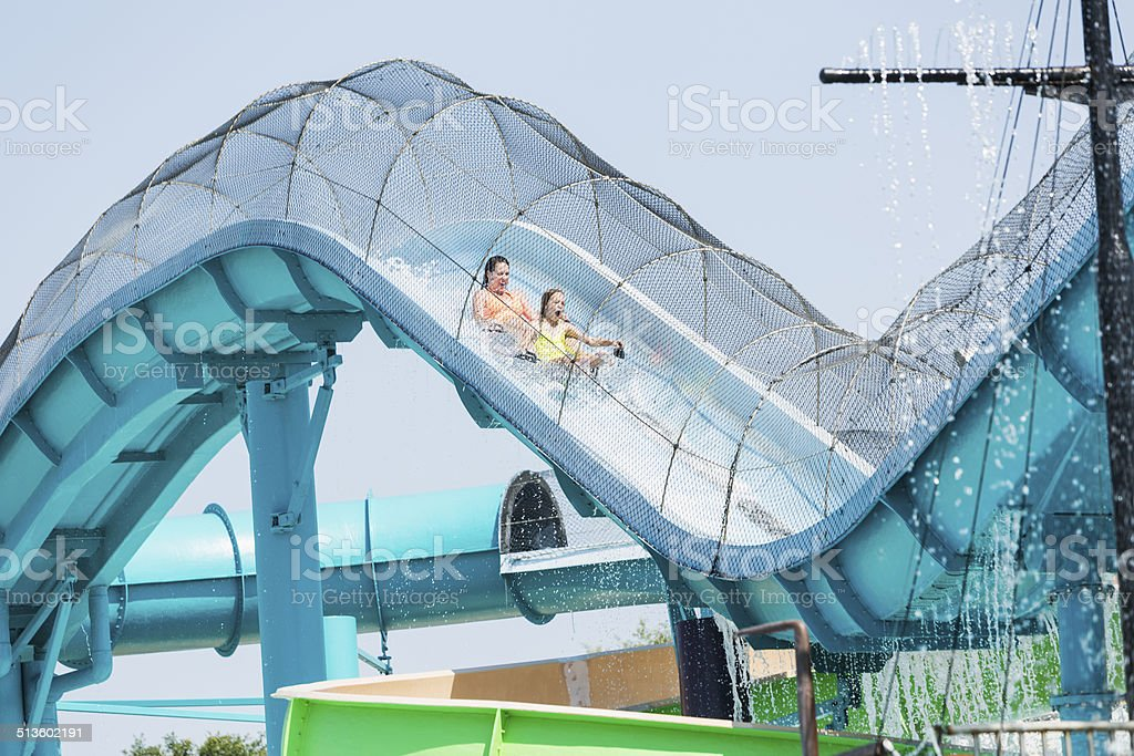 Mother and daughter on water slide stock photo