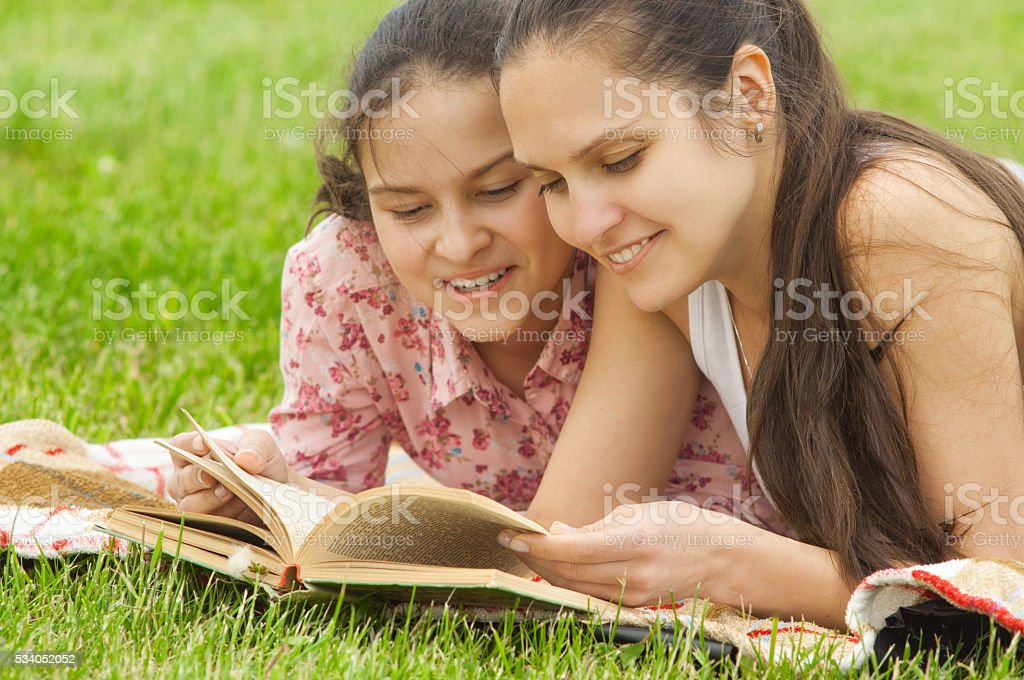 mother and daughter outdoor reading book stock photo