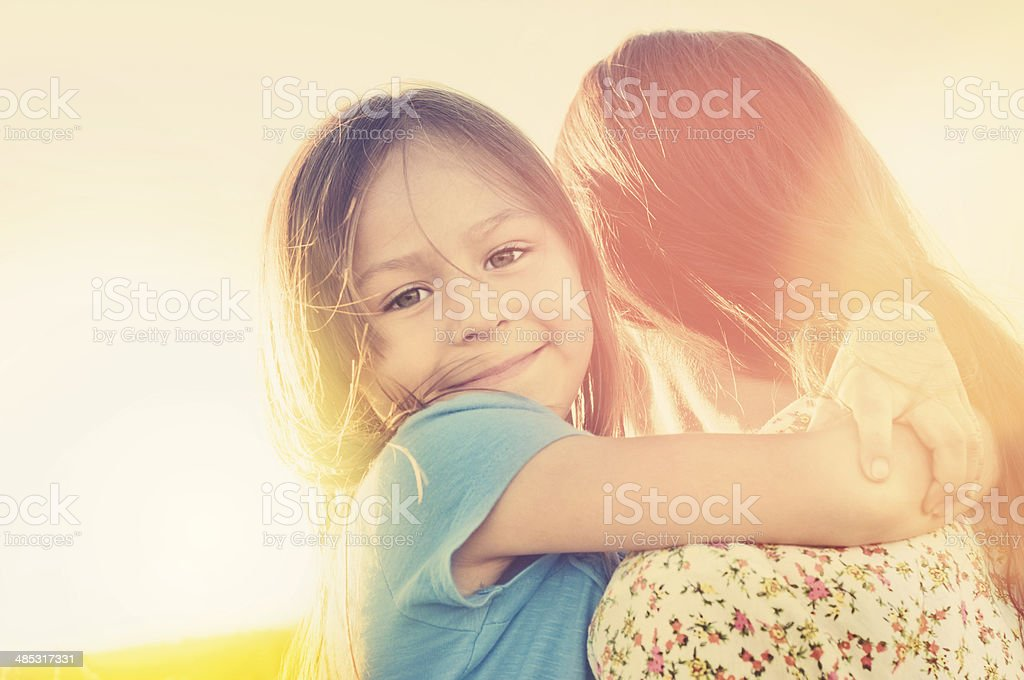 Mother and daughter outdoors in sunlight stock photo