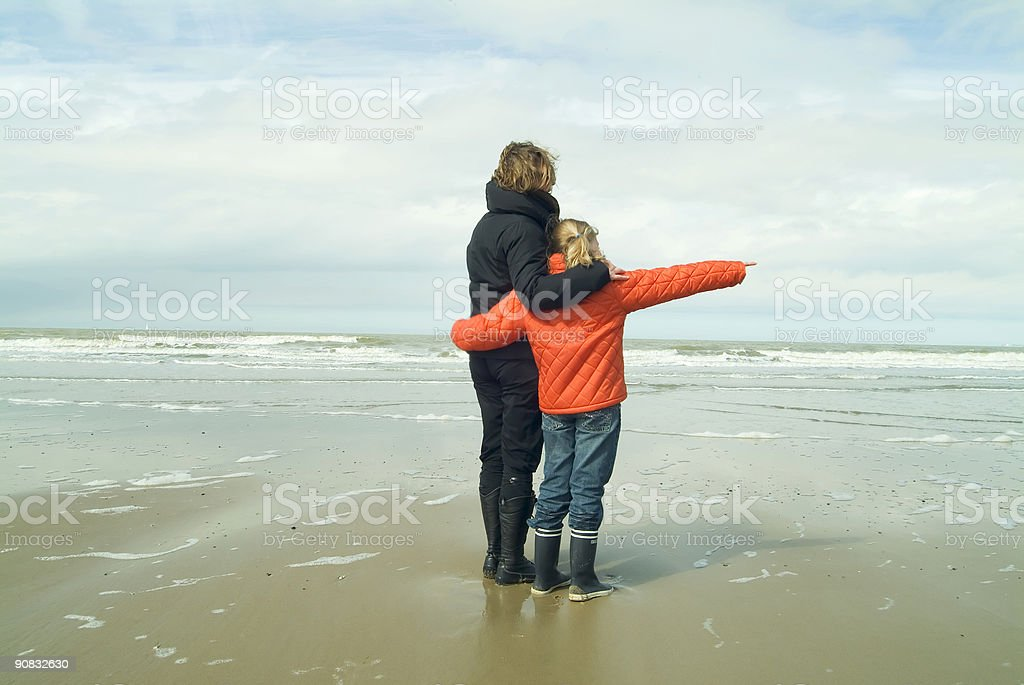 mother and daughter overlooking the sea stock photo