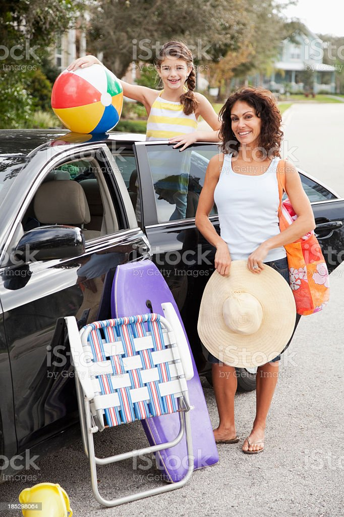 Mother and daughter packing car for trip to beach stock photo