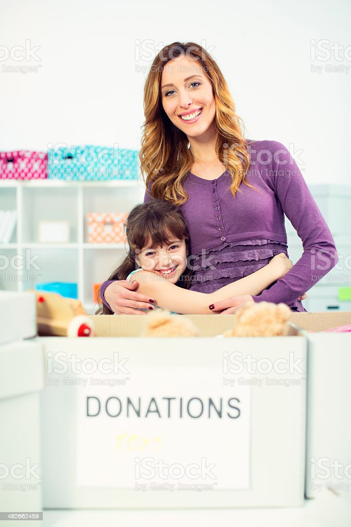 Mother and daughter packing donation box. royalty-free stock photo
