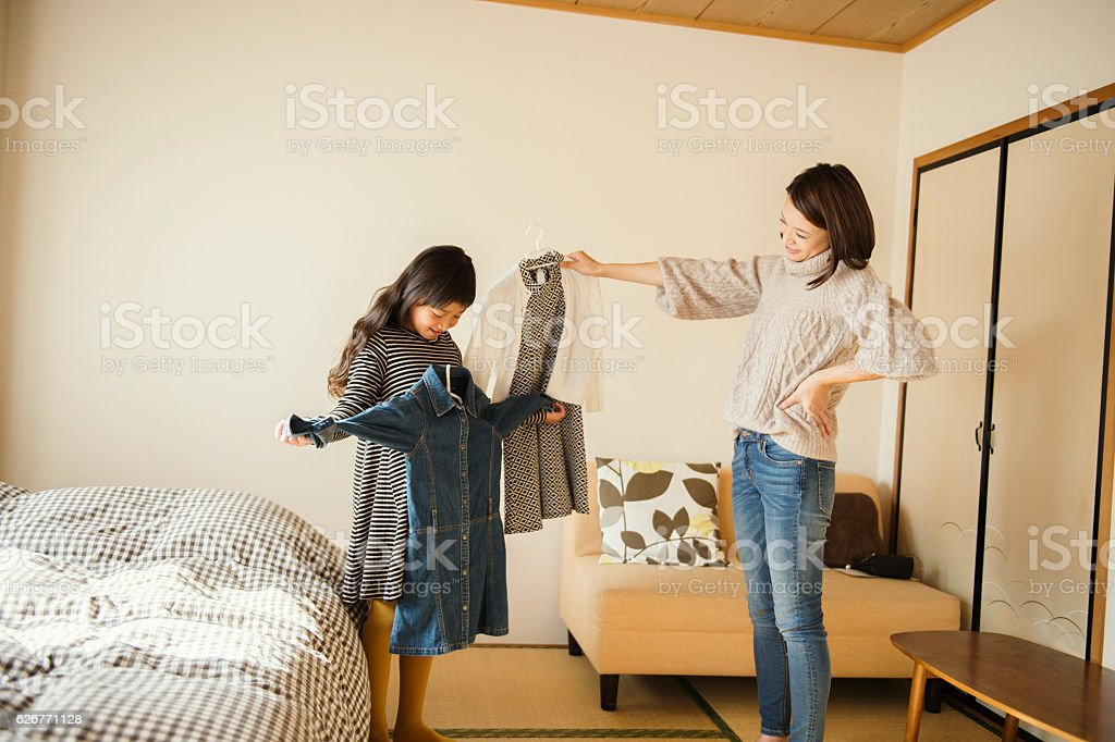 Mother and daughter picking out clothes in bedroom stock photo
