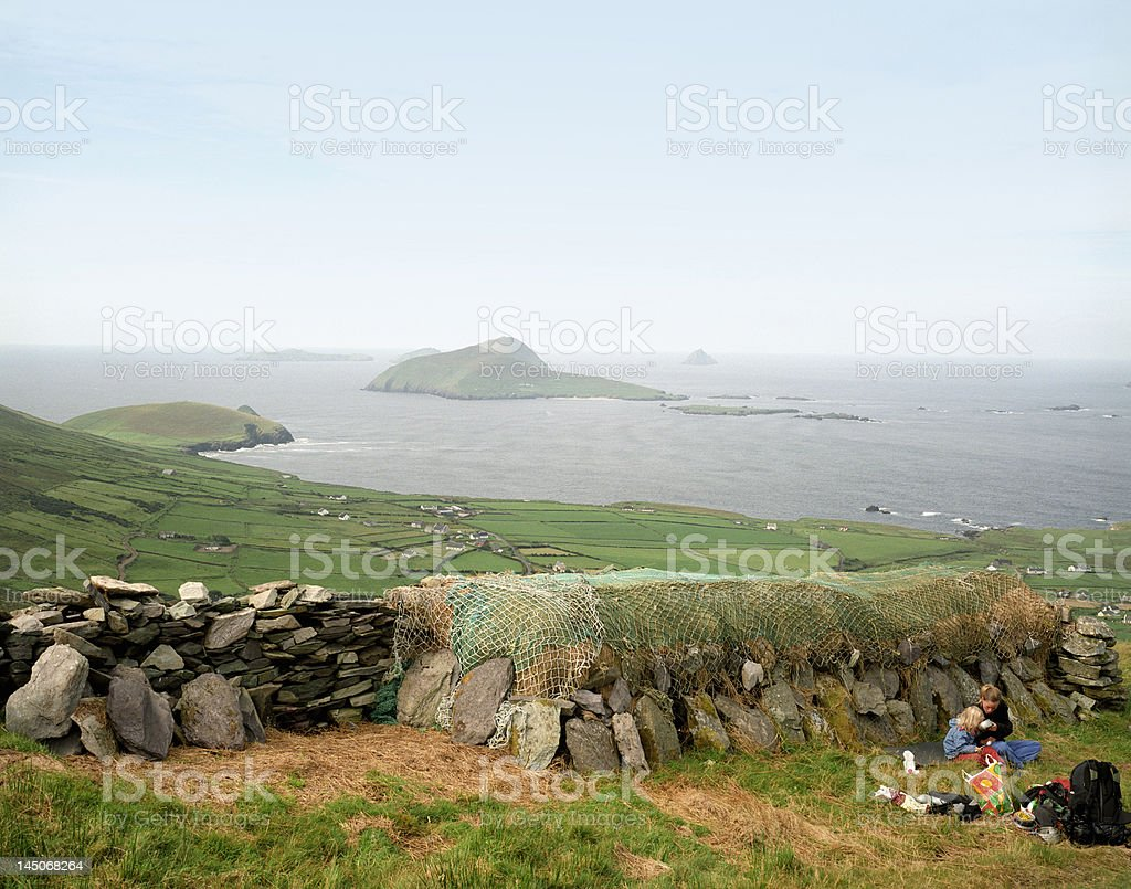 Mother and daughter picnicking in field stock photo