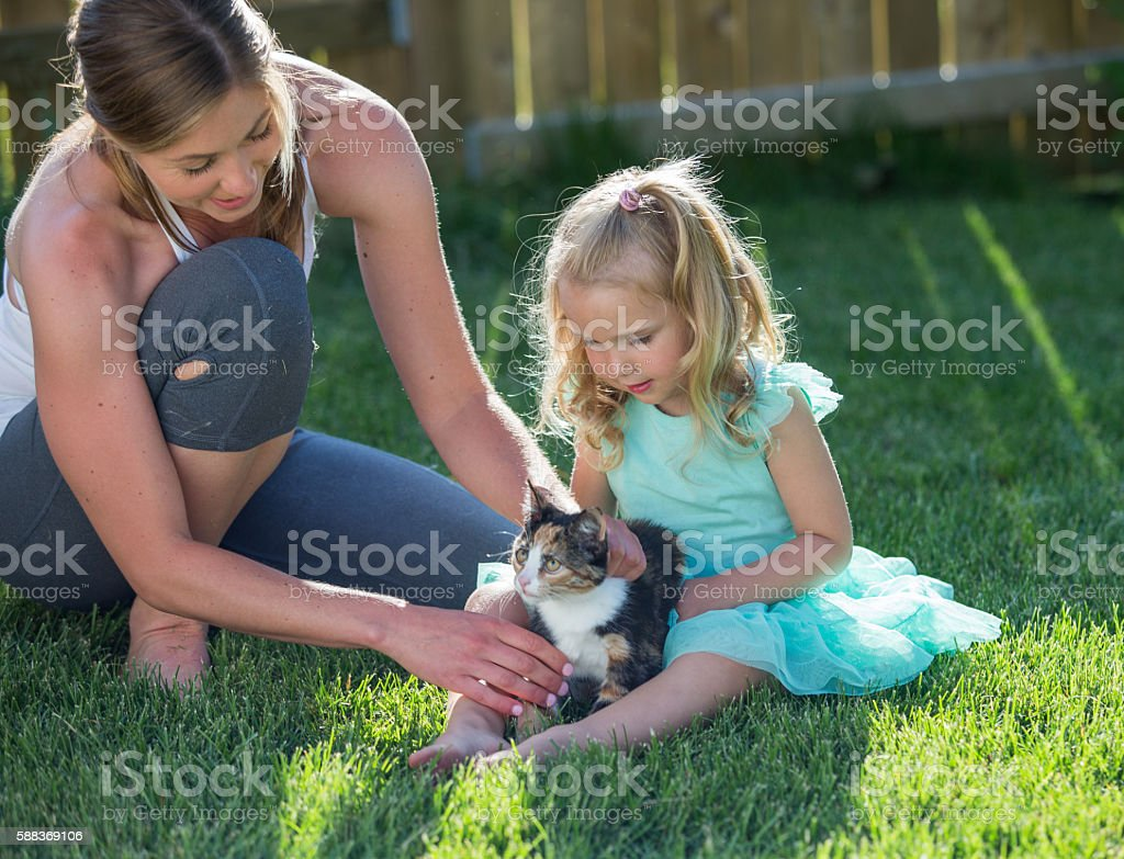Mother and daughter play with a kitten outside stock photo