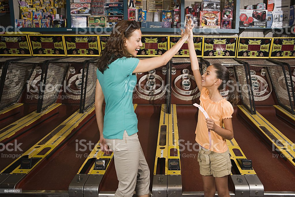 Mother and daughter playing arcade game stock photo