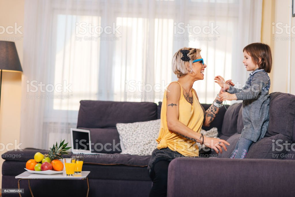 Mother and daughter playing at home with disguise eye wear  and having fun stock photo