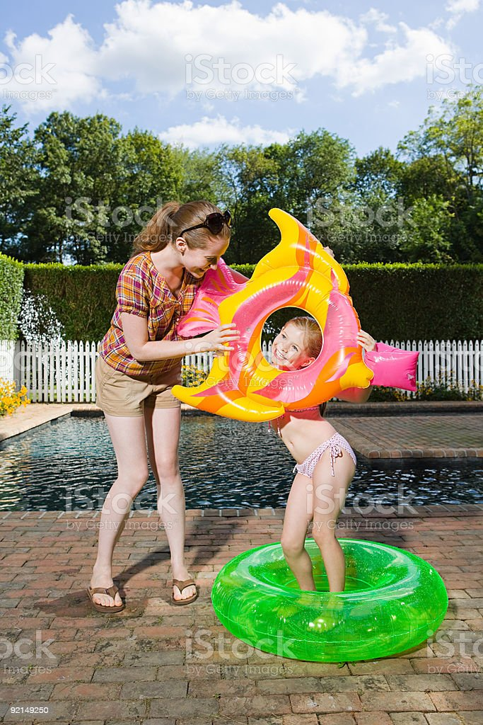 Mother and daughter playing by swimming pool royalty-free stock photo