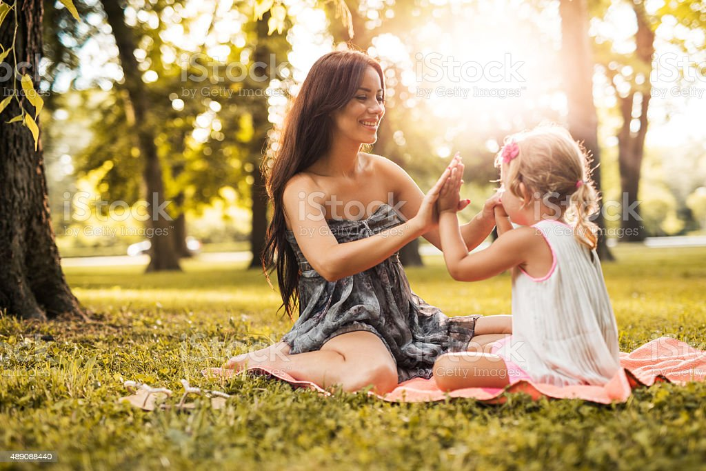 Mother and daughter playing clapping game during spring day. stock photo