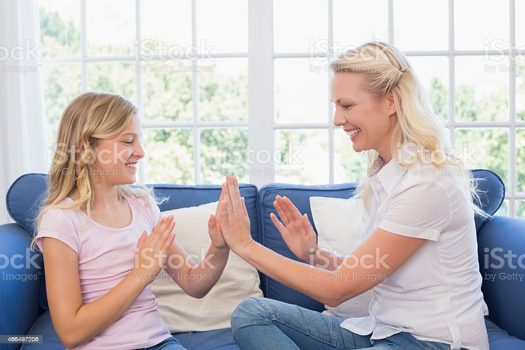 Mother and daughter playing clapping game on sofa stock photo