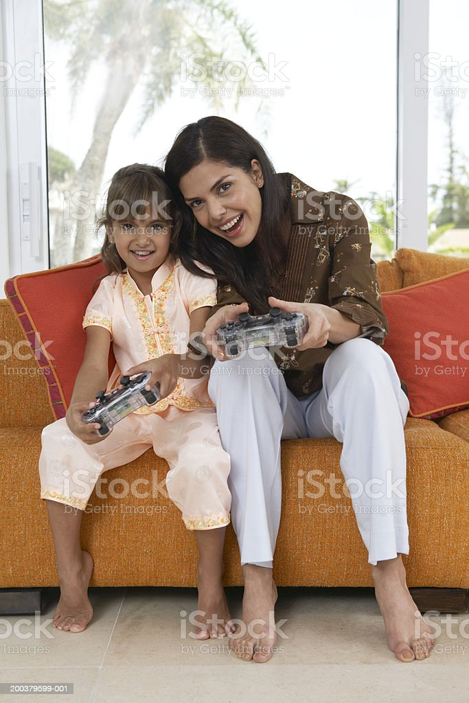 Mother and daughter (7-9) playing game with hand held controls royalty-free stock photo