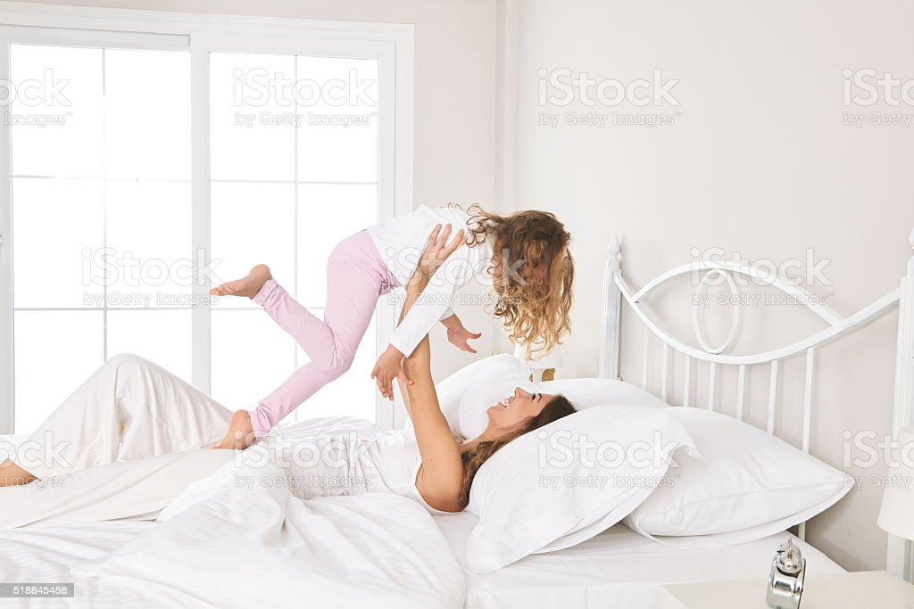 Mother and daughter playing in bed stock photo