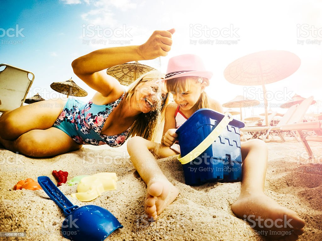 Mother and daughter playing on beach with sand and toys stock photo