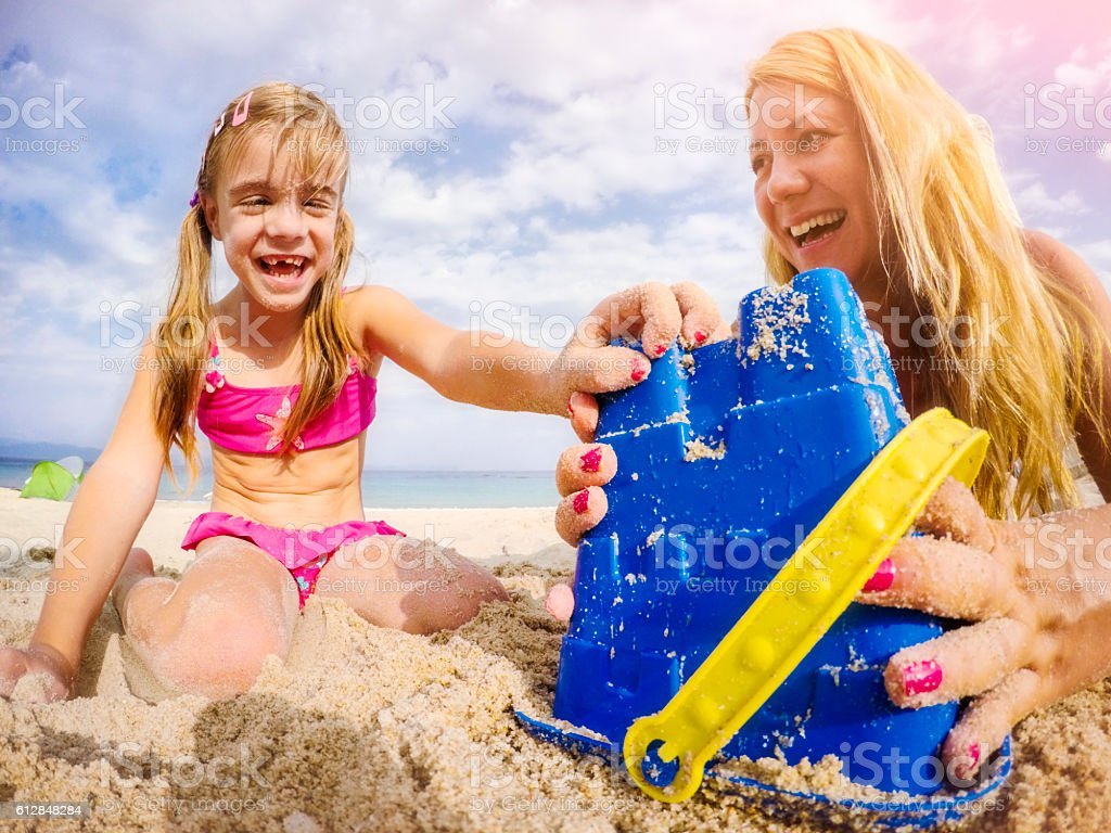 Mother and daughter playing on beach with sand pail stock photo