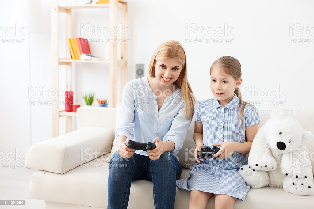 Mother and daughter playing on console stock photo