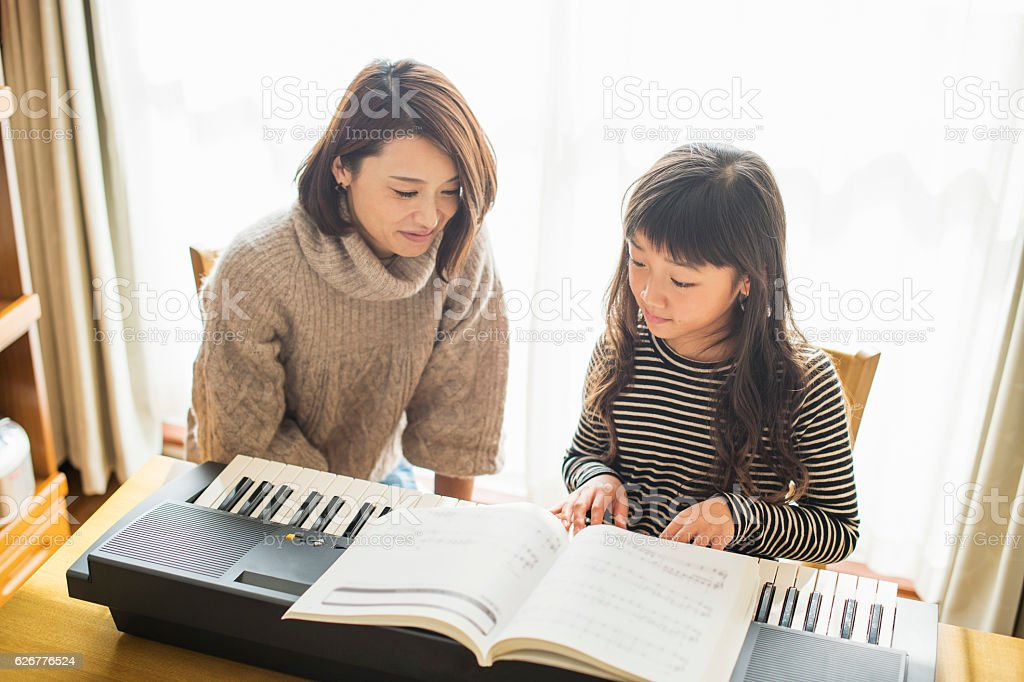 Mother and daughter playing  on electronic piano stock photo