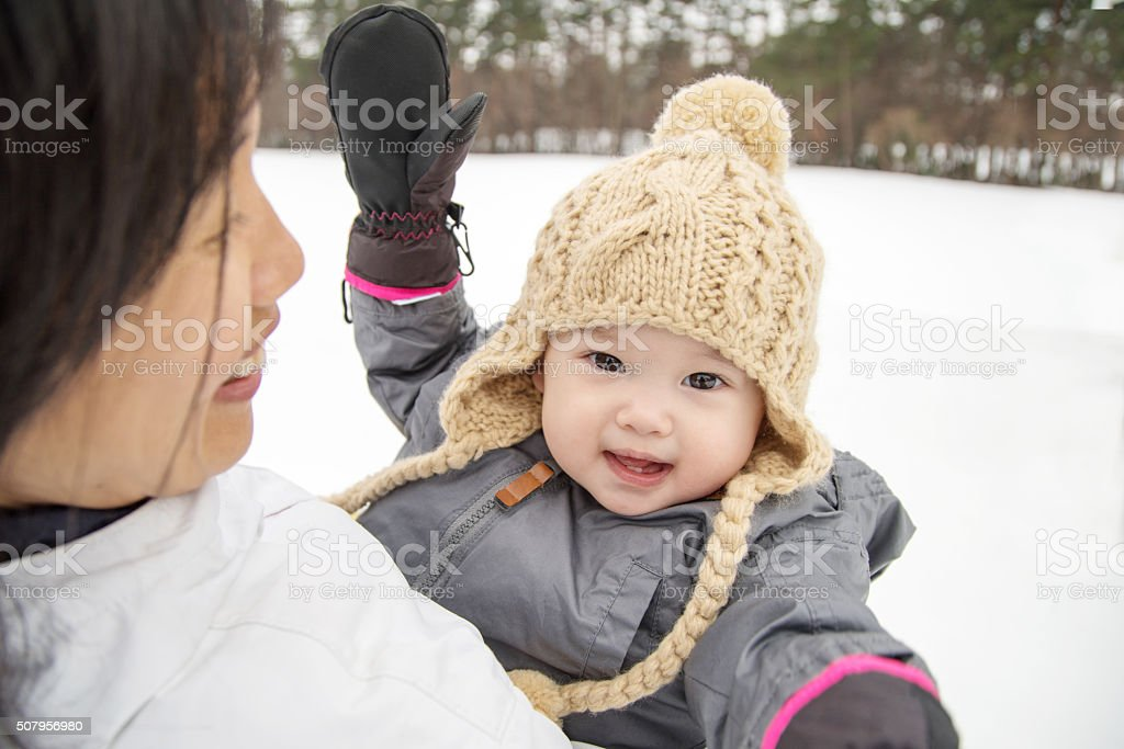 Mother and Daughter playing outside in the snow stock photo