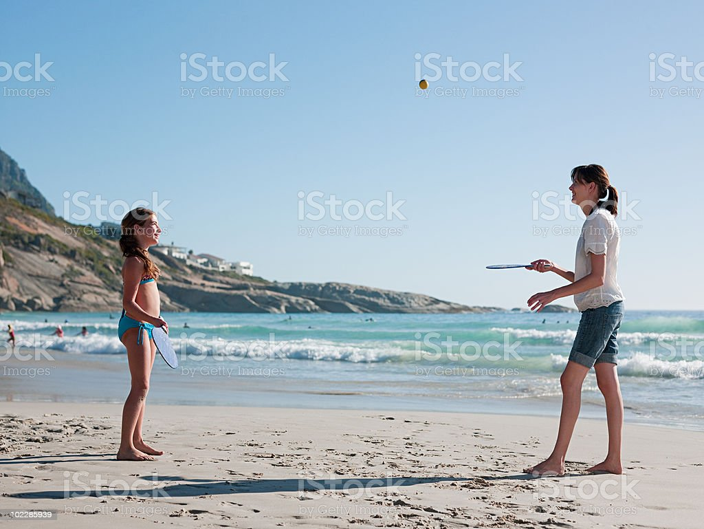 Mother and daughter playing paddleball on beach stock photo