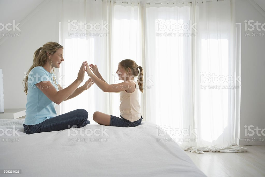 Mother And Daughter Playing Patty-Cake On Bed stock photo