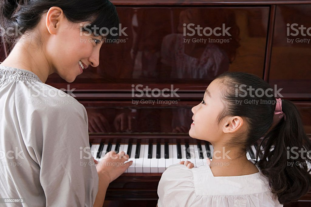 Mother and daughter playing the piano stock photo
