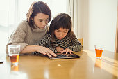 Mother and daughter playing with a digital tablet in house