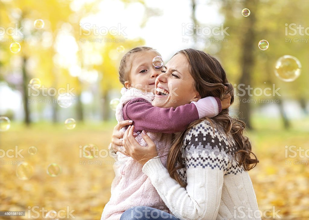 Mother and daughter playing with bubbles outside royalty-free stock photo
