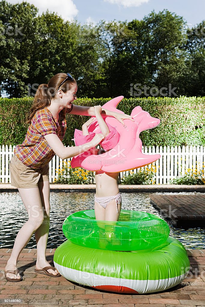 Mother and daughter playing with inflatable rings royalty-free stock photo