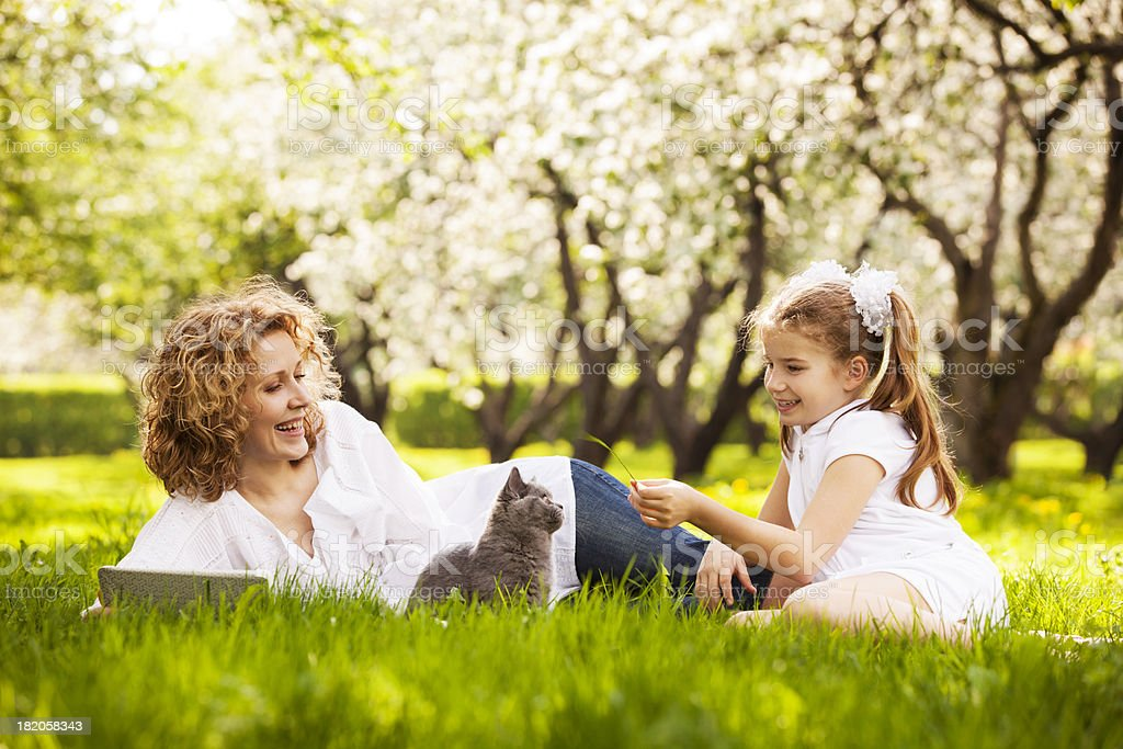 Mother and daughter playing with kitten on lawn in park stock photo