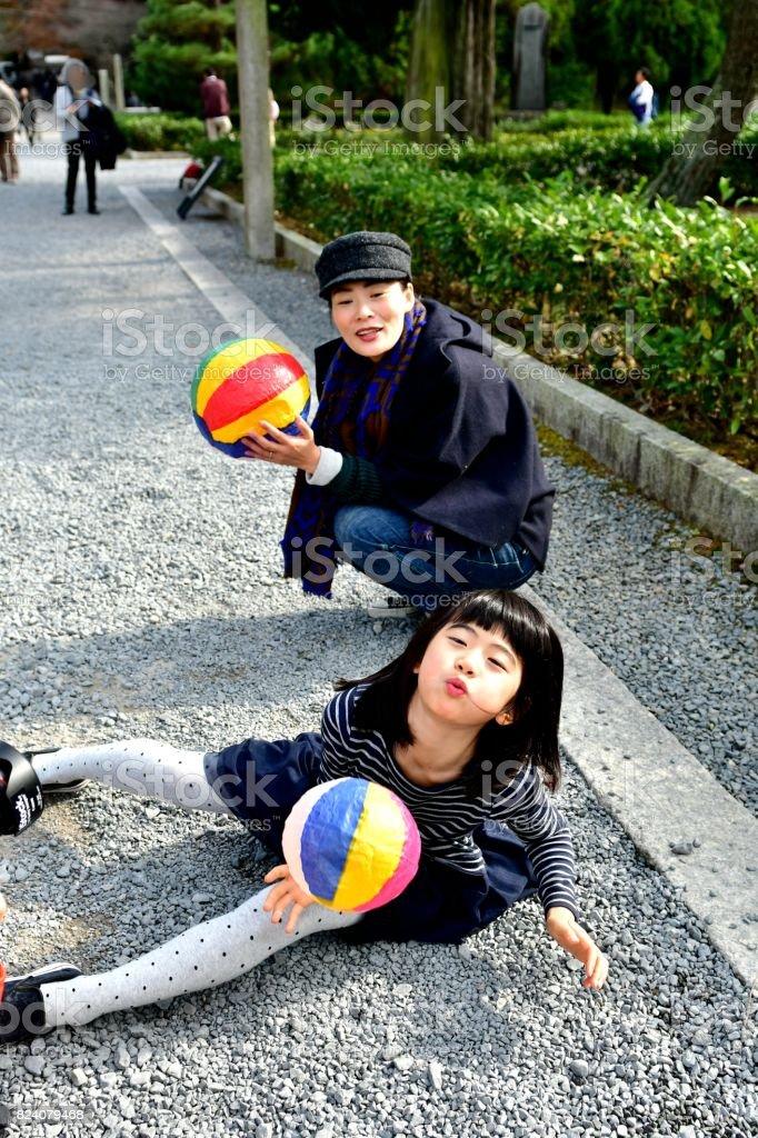 Mother and Daughter Playing with Paper Balloonn at Tofuku-ji, Kyoto stock photo