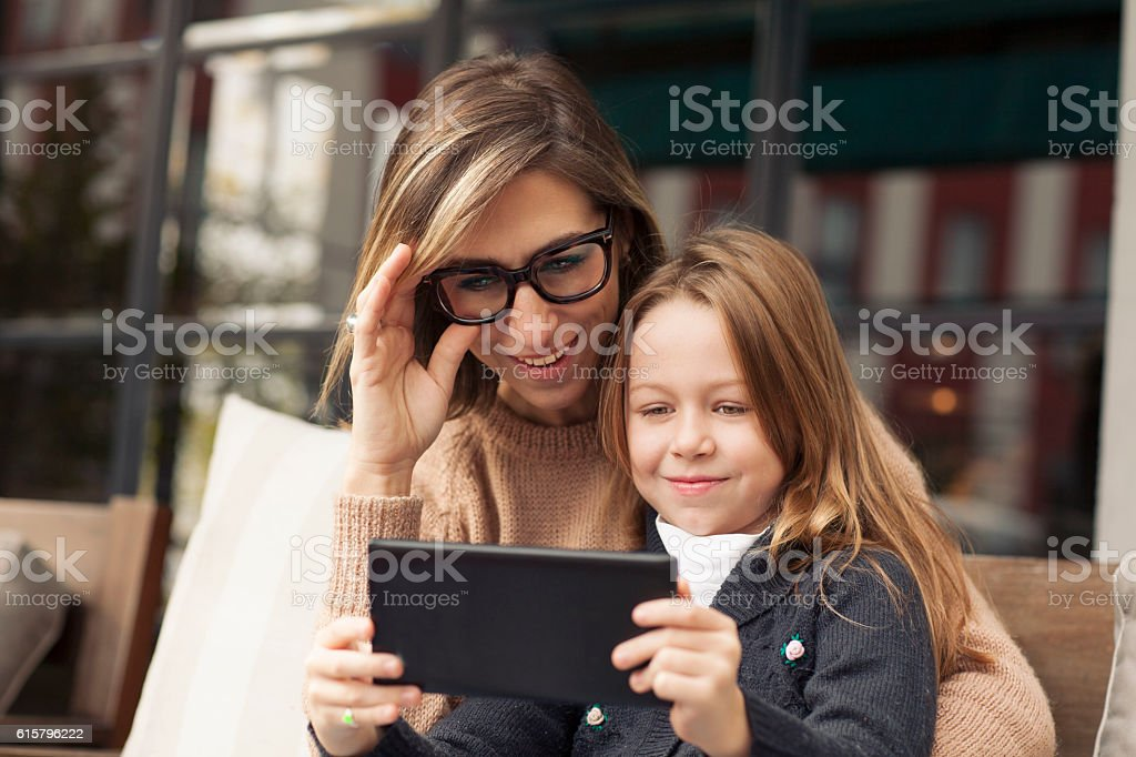 Mother and daughter playing with tablet stock photo