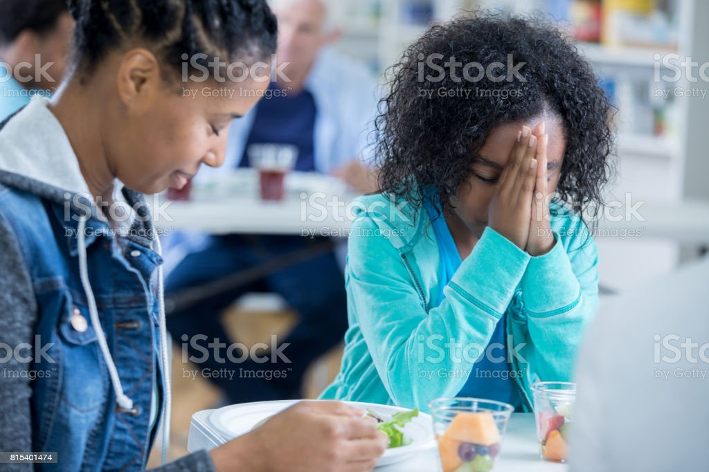 Mother and daughter pray before eating meal in soup kitchen stock photo