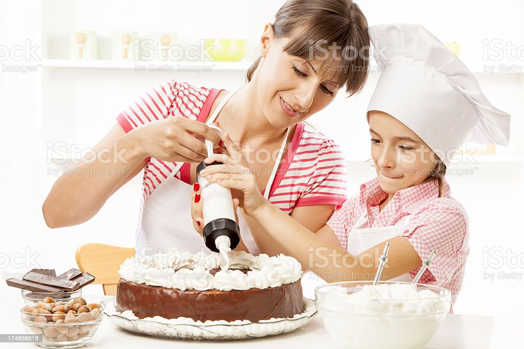 Mother and daughter preparing chocolate cake stock photo
