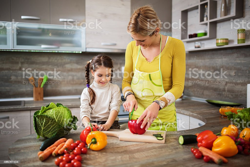 Mother and daughter preparing food in the kitchen. stock photo