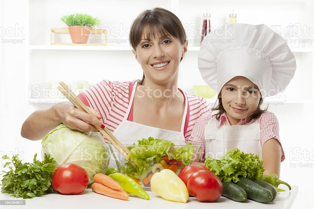 Mother and daughter preparing fresh vegetable salad royalty-free stock photo
