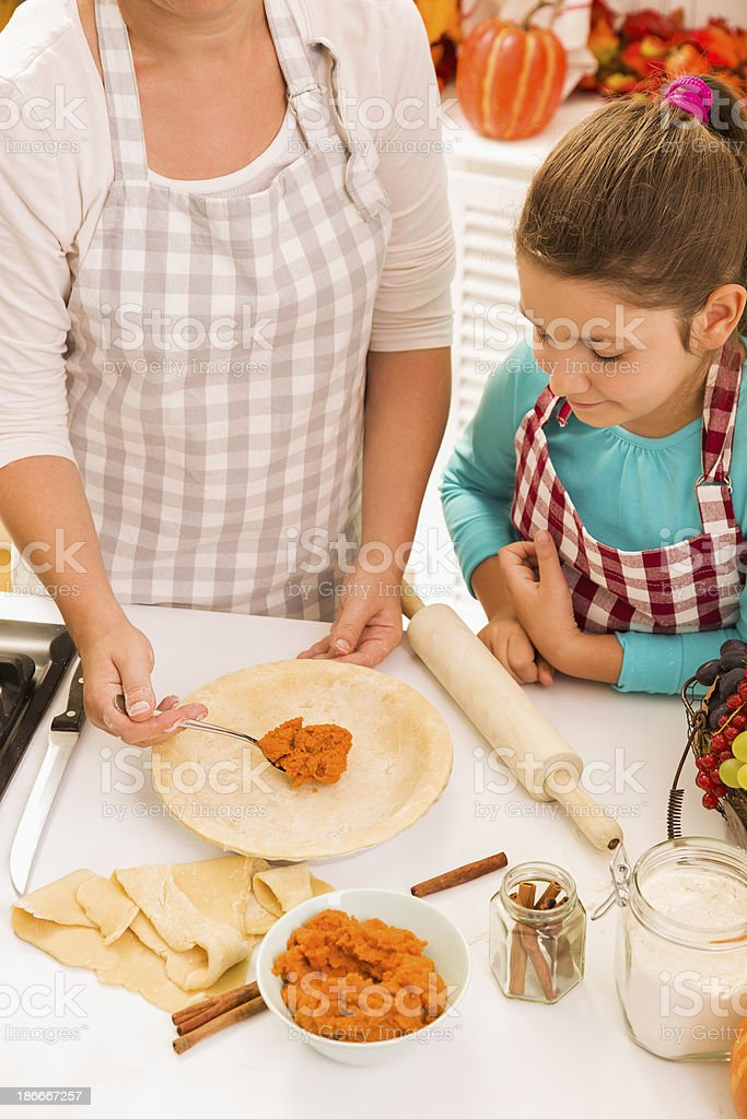 Mother and daughter preparing pumpkin pie royalty-free stock photo