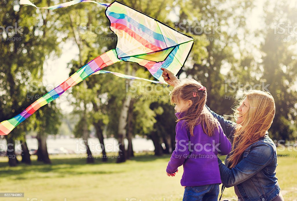 Mother and daughter preparing the kite to fly stock photo