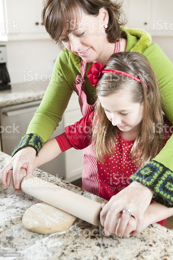 Mother and Daughter Pushing Rolling Pin Together, Working Cookie Dough stock photo