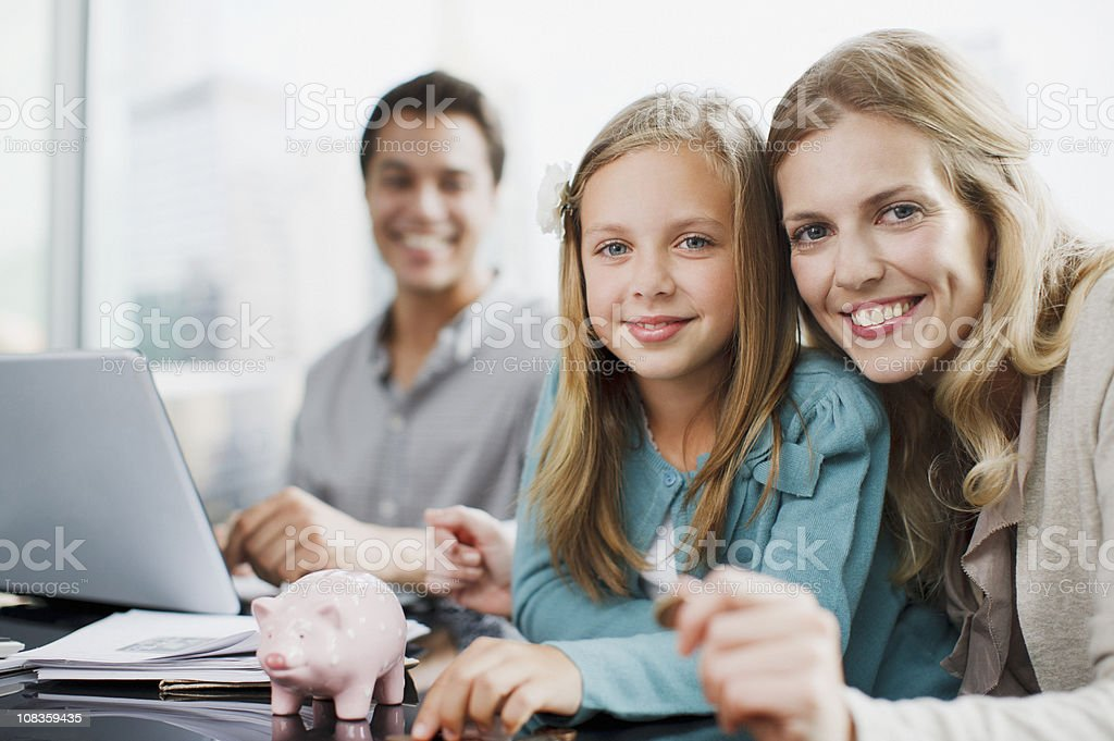 Mother and daughter putting coins into piggy bank royalty-free stock photo